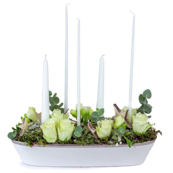 Centre de table blanc avec des roses blanches, du freesia blanc , du feuillage et des bougies
