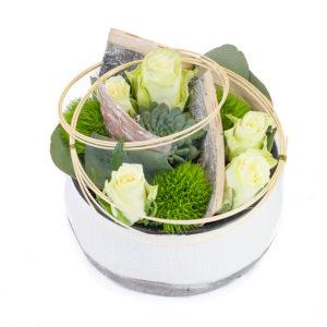 Composition ronde avec des roses blanches, une succulente, des œillets