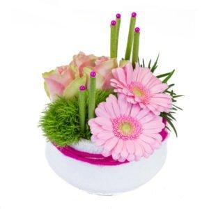 Composition ronde avec des roses roses, des germinis roses avec un travail de feuillage et accessoires.