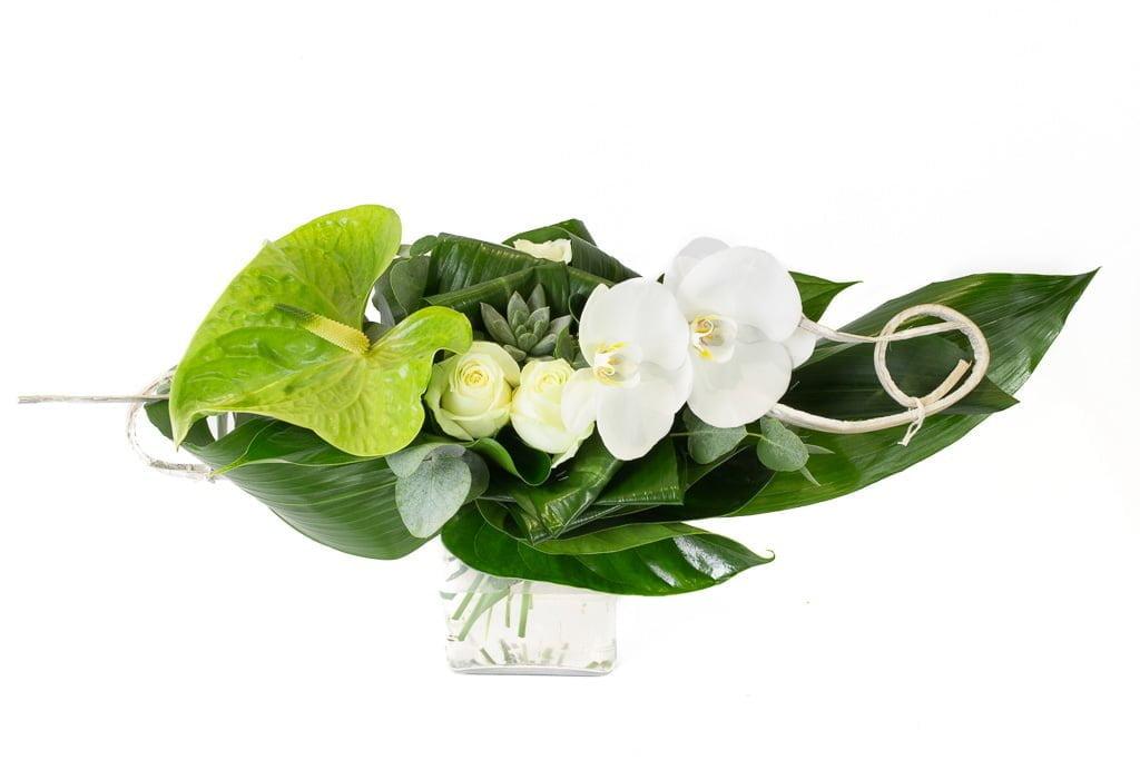 Bouquet en longueur avec des roses blanches, des orchidées blanches, anthurium vert, une crassulacée, des bois et un travail de feuillage.